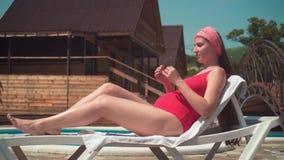 Uma menina grávida bonita em um roupa de banho de uma peça só vermelho está encontrando-se em um vadio pela associação A menina v vídeos de arquivo
