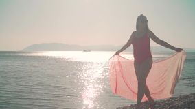 Uma menina grávida em um roupa de banho de uma peça só vermelho anda ao longo do litoral nos raios do sol de ajuste video estoque