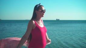 Uma menina grávida em um roupa de banho de uma peça só vermelho e em caminhadas dos vidros ao longo do litoral e dos sorrisos vídeos de arquivo
