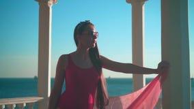 Uma menina grávida em um roupa de banho de uma peça só vermelho e suportes dos vidros na praia em um miradouro concreto branco filme