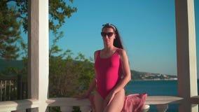 Uma menina grávida em um roupa de banho de uma peça só vermelho e suportes dos vidros na praia em um miradouro concreto branco vídeos de arquivo