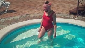 Uma menina grávida em um roupa de banho de uma peça só vermelho e em vidros está knee-deep na água da associação video estoque