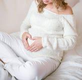 Uma menina grávida guarda as mãos na forma de um coração fotografia de stock royalty free