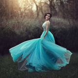 Uma menina graduada bonita está girando em um vestido azul Jovem mulher elegante em um vestido bonito no parque Foto da arte Foto de Stock