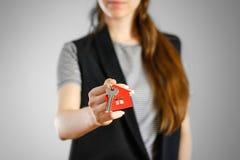 Uma menina guarda as chaves à casa Casa do vermelho da porta-chaves Fotografia de Stock Royalty Free