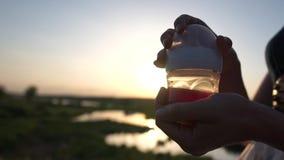 Uma menina guarda uma garrafa de bebê com compota no fundo de uma natureza no por do sol vídeos de arquivo