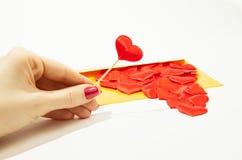 Uma menina guarda um coração em sua mão, ao lado de um envelope do ouro e de muitos corações, uma situação do amor na distância fotografia de stock royalty free