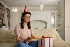 Uma menina infeliz que veste um chapéu em seu aniversário com um bolo com c fotos de stock royalty free