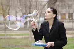 Uma menina infla uma bolha grande na rua Fotos de Stock