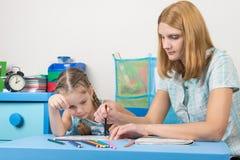 Uma menina interessou o olhar como pinturas da mamã um estêncil Fotos de Stock