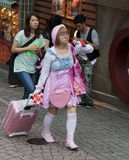 Uma menina japonesa nova vestiu-se no rosa em caminhadas de um estilo do kawaii dentro fotos de stock royalty free