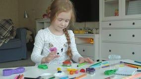Uma menina joga com plasticine, bolas de rolos, lá é figuras e lápis coloridos no desktop, o desenvolvimento filme