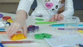 Uma menina joga com plasticine, bolas de rolos, lá é figuras e lápis coloridos no desktop, o desenvolvimento video estoque