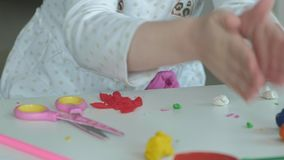 Uma menina joga com plasticine, bolas de rolos com suas mãos, há umas figuras e lápis coloridos no desktop filme