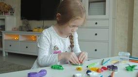 Uma menina joga com plasticine, corta figuras fora da forma, figuras e os lápis coloridos encontram-se no desktop filme