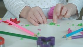 Uma menina joga com plasticine, esculpe uma figura, lá é figuras e lápis coloridos no desktop, video estoque