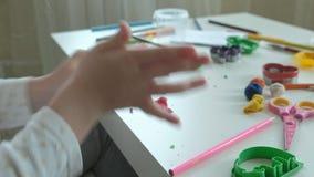 Uma menina joga com plasticine, separa em partes pequenas, no desktop é figuras e lápis coloridos, filme