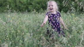 Uma menina joga na grama alta no por do sol video estoque
