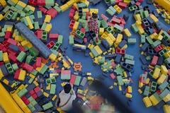 Uma menina joga no grande LEGO Imagens de Stock
