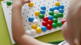Uma menina joga um jogo, dá certo um mosaico multi-colorido que se torne, desenvolvendo habilidades de motor e pensando dentro filme
