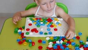 Uma menina joga um jogo, dá certo um mosaico multi-colorido que se torne, desenvolvendo habilidades de motor e pensando dentro video estoque