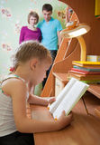 Uma menina lê um livro Fotos de Stock Royalty Free
