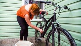 Uma menina lava uma bicicleta perto da casa vídeos de arquivo