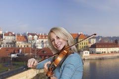 Uma menina loura bonita no vestido preto com bordos vermelhos joga uma imagem do violino no fundo da cidade foto de stock