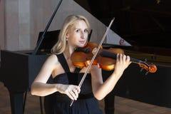 Uma menina loura bonita no vestido preto com bordos vermelhos joga um violino foto de stock royalty free