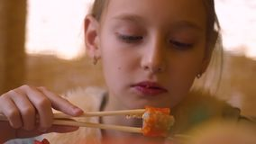 Uma menina loura bonita nova que come o sushi no café ou em um restaurante japonês filme