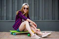 Uma menina loura bonita que veste óculos de sol, camisa quadriculado e short da sarja de Nimes está sentando-se nos logboards bri fotografia de stock royalty free
