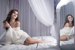 Uma menina loura bonita 'sexy' bonito em uma camiseta feita malha em uma cama branca senta os pés curvados Olha sua reflexão no e Imagem de Stock