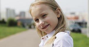 Uma menina loura bonito está com um 'trotinette' nas ruas ao longo da estrada na cidade video estoque