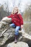 Uma menina loura da criança bonito que levanta em uma rocha fora Foto de Stock
