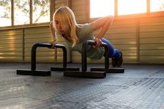 Uma menina loura em um t-shirt azul e em caneleiras treina no gym o fotografia de stock royalty free
