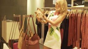 Uma menina loura escolhe e tenta sobre bolsas em uma loja de roupa video estoque