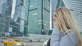 Uma menina loura está falando no telefone no fundo dos arranha-céus e dos prédios no centro da cidade vídeos de arquivo