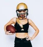 Uma menina loura incredibly bonita em um capacete que levanta em um equipamento preto e que guarda uma bola esporte Fósforo ameri fotografia de stock royalty free