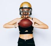 Uma menina loura incredibly bonita em um capacete que levanta em um equipamento preto e que guarda uma bola esporte Fósforo ameri foto de stock royalty free