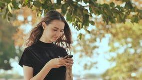 Uma menina loura nova do russo escreve uma mensagem no telefone em um parque do verão video estoque