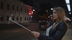 Uma menina loura nova faz um selfie fotografar usando uma vara da vara Viva e crie histórias para redes sociais vídeos de arquivo