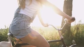 Uma menina loura nova nas calças na bicicleta retro que vai abaixo da estrada no campo video estoque