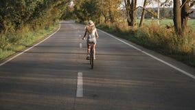 Uma menina loura nova nas calças na bicicleta retro que vai abaixo da estrada no campo filme