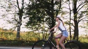 Uma menina loura nova nas calças na bicicleta retro que vai abaixo da estrada no campo vídeos de arquivo