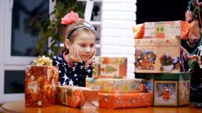 Uma menina loura pequena bonita, com uma curva cor-de-rosa em seu cabelo, em um beautifu, l festivo, vestido elegante está olhand video estoque