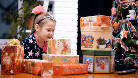 Uma menina loura pequena bonita, com uma curva cor-de-rosa em seu cabelo, em um beautifu, l festivo, vestido elegante está olhand filme