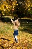 Uma menina loura que joga acima as folhas Fotografia de Stock Royalty Free