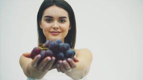 Uma menina magro bonita come frutos saudáveis Durante isto, uma jovem mulher bonita aumenta um ramalhete maduro da uva em suas mã video estoque