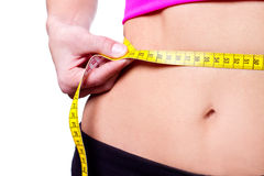 Uma menina magro que mede sua cintura Imagens de Stock