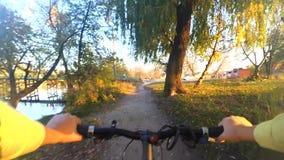 Uma menina monta uma bicicleta na terra em um campo do outono filme